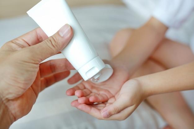 위생 및 바이러스 백신 박테리아에 대한 아기 손 청소를 위해 플라스틱 병에서 알코올 젤을 적용하는 어머니 손. 총을 닫습니다.
