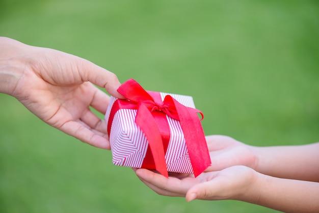 그녀의 아이에게 선물 상자를주는 어머니 손