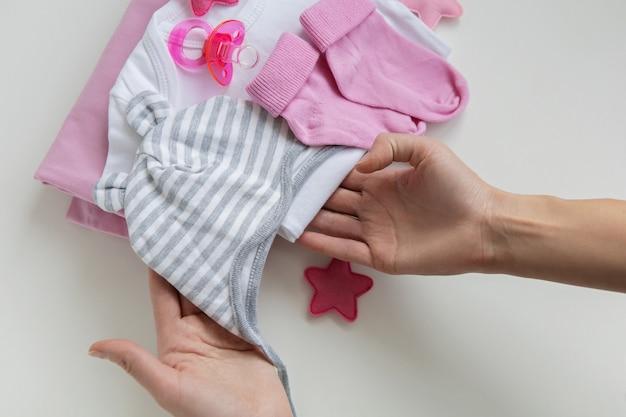 Мать за руку держит детскую шапочку будущей дочери ребенка