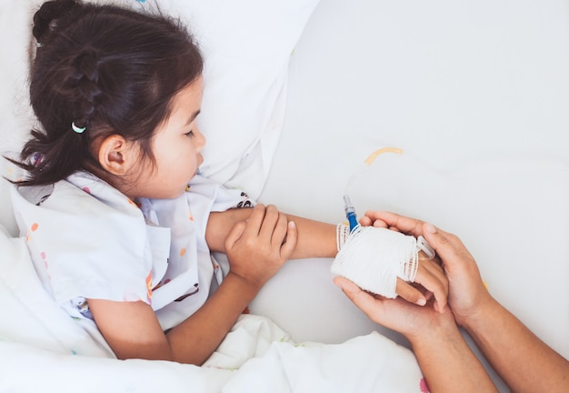 Mother hand holding sick daughter hand who have iv solution bandaged