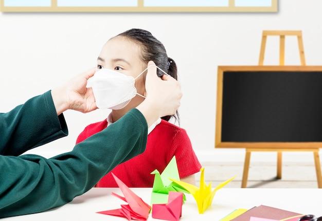 교실에서 딸에게 마스크를 씌우는 어머니 손
