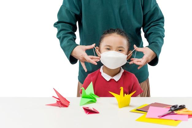 白い背景の上に分離された娘にマスクを置く母の手