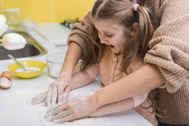 Mother and happy daughter putting flour on table