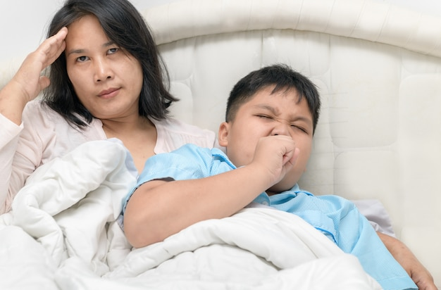 Mother has a headache because her son is sick and coughs.