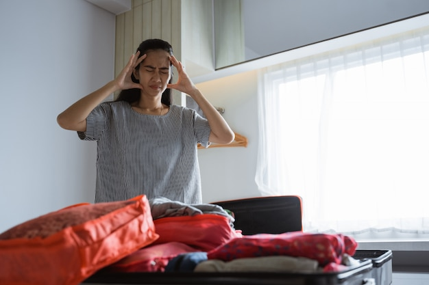 Mother has a headache when preparing clothes and bags