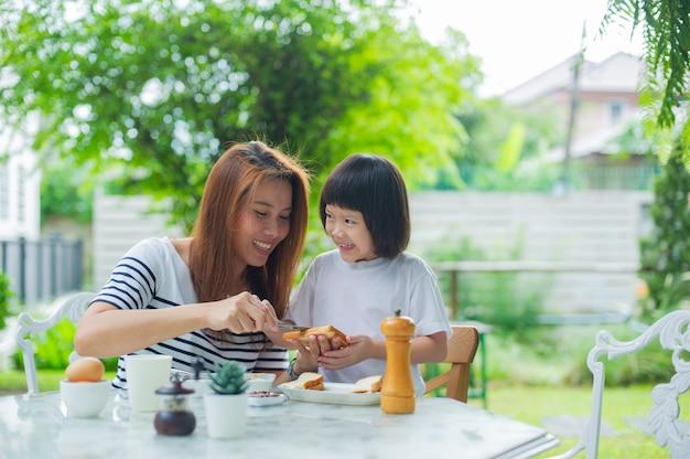 어머니는 자녀와 함께 아침을 먹습니다.