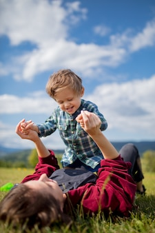 Mother have a fun with a son on a meadow in mountains