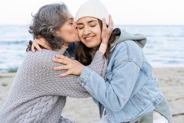 ビーチで娘と優しいひとときを過ごす母