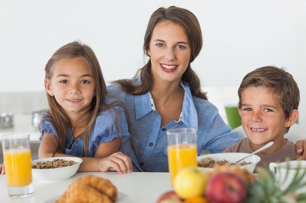 彼女の子供たちと朝食を食べる母親