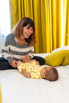 침실에 있는 침대에서 아기와 즐거운 시간을 보내는 어머니, 4개월 된 아기와 처음으로 젊은 백인, 세로 사진