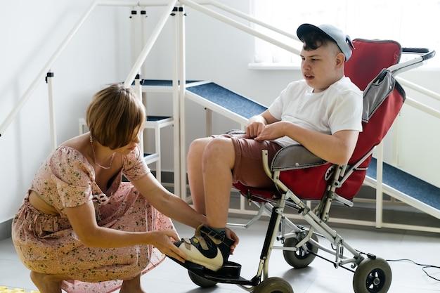 母は車椅子の脳性麻痺障害のある少年を助けます