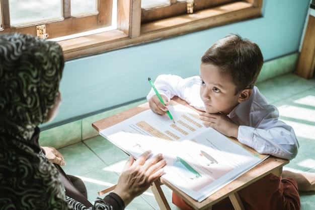 母は子供が宿題をするのを手伝います