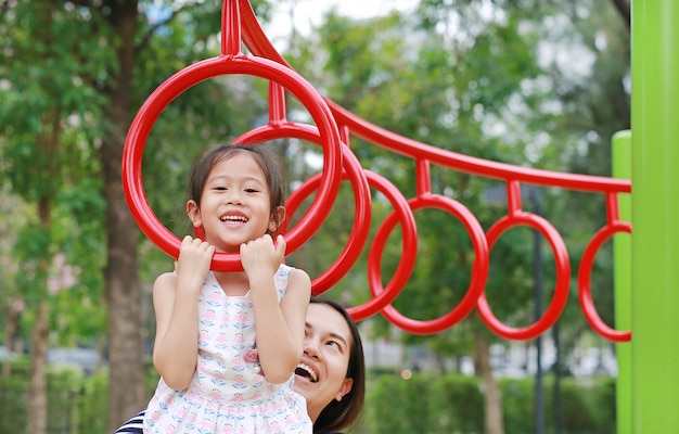 Mother help her daughter to playing on gymnastic ring on playground outdoor.