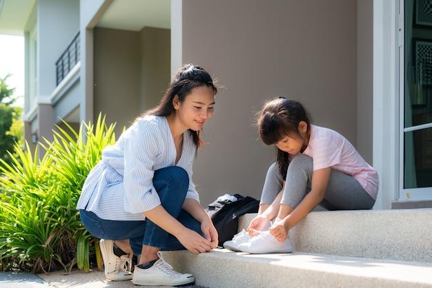 母は娘の小学生を制服姿で家の前で靴ひもを履くのに役立ちます