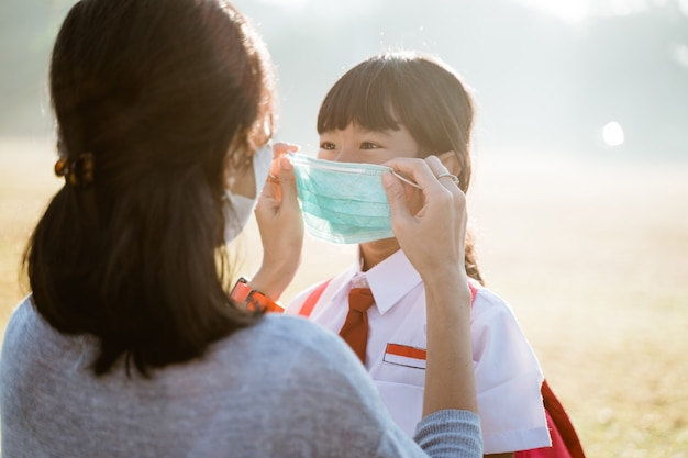 Mother help her daughter to put on the mask before going to school
