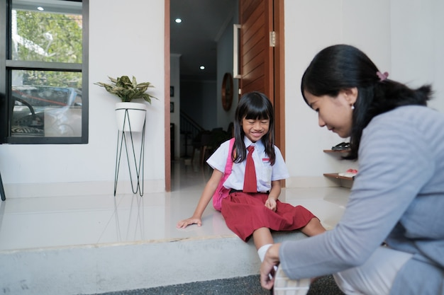 Mother help her daughter to wear a shoes in the morning while preparing to go to school