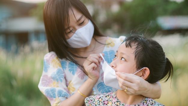 母は保護のためにフェイスマスクを着ている娘を助けます2019-ncov、covid 19またはコロナウイルス