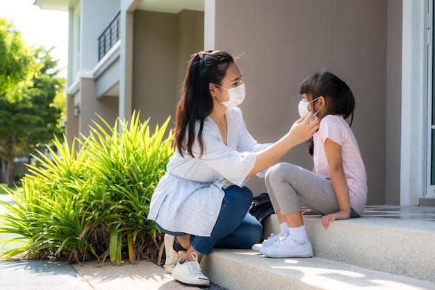 母親は医療マスクを着ている彼女の娘を助ける