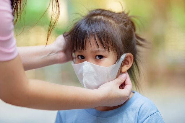 Mother help kids wearing the mask for protect from virus and air pollution.