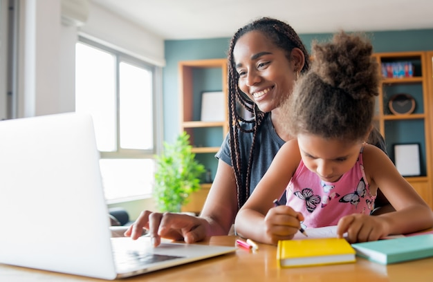 어머니는 집에 머무르는 동안 온라인 학교로 딸을 돕고 지원합니다. 새로운 정상적인 라이프 스타일 개념. monoparental 개념.