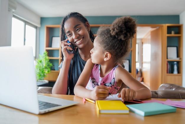 自宅で電話で話している間、母親はオンラインスクールで娘を助け、サポートしています。新しい通常のライフスタイルのコンセプト。一人親の概念。