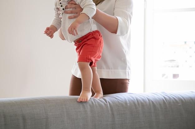 赤ちゃんが自宅のソファの上を歩くのを手伝っている母親。ママのサポートで最初の一歩を踏み出す子供。クロップドショット。親子関係の概念