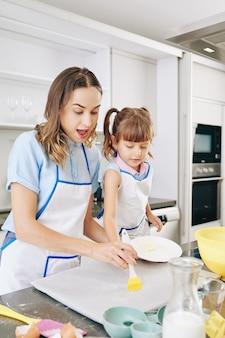 Мать помогает дочери силиконовой кистью нанести топленое масло на пергаментную бумагу