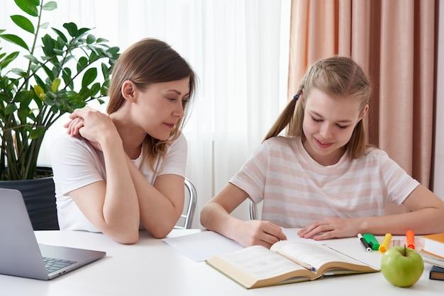 Мать помогает дочери делать домашнее задание. концепция домашнего образования в карантине. трудности дистанционного обучения