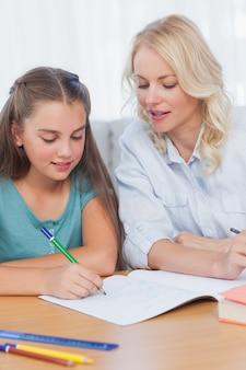 Мать, помогая дочери с домашней работой