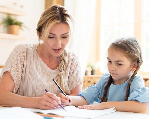 Мать помогает дочери с домашним заданием