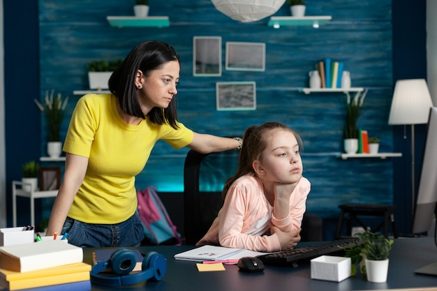 Mother helping daughter with school homework analyzing mathematics online course