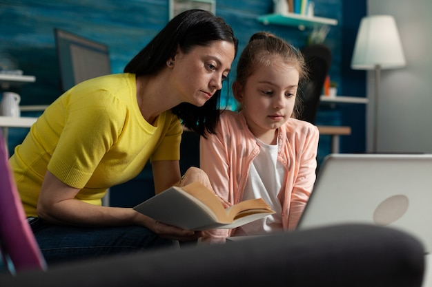 Mother helping daughter with school homework reading literature book