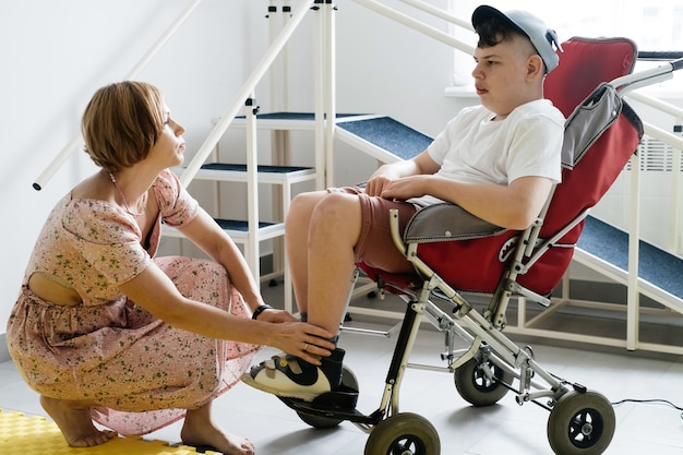 脳性麻痺の車椅子の障害のある少年が靴を履くのを手伝っている母親