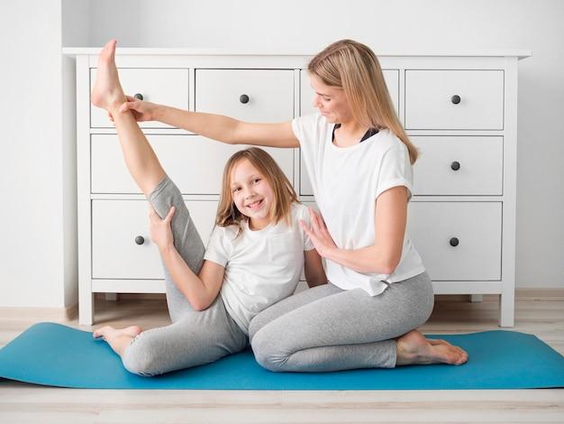 Мать помогает девушке растянуть