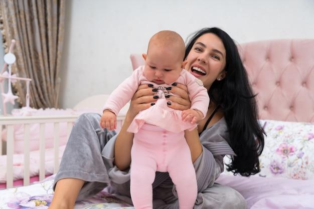 母親は赤ちゃんが立つのを手伝い、胸を抱き、ピンクのリネンでベッドに座り、カメラを見て笑いました。