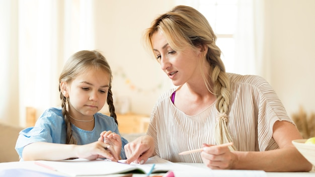 娘が宿題をするのを手伝う母親