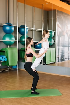 Mother helping her daughter to do exercises in gym