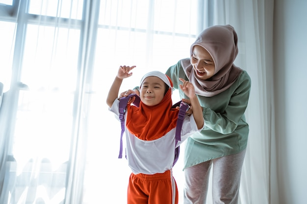 Mother helping her daughter preparing school