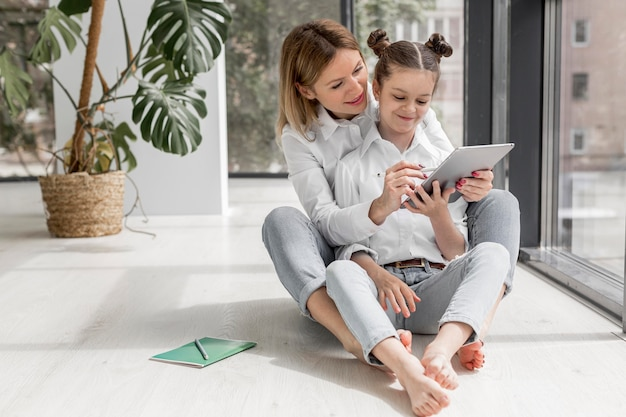 Madre che aiuta sua figlia a studiare al chiuso