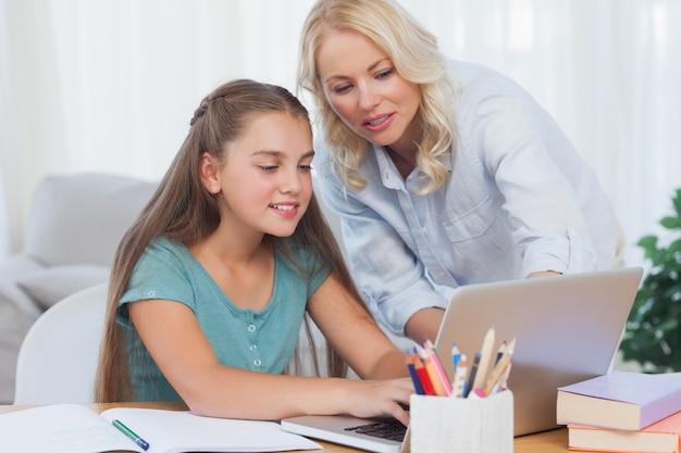 Мать помогает своей дочери сделать домашнее задание