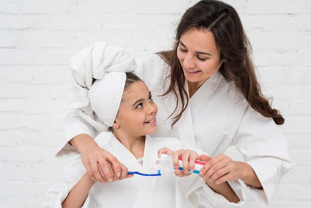 Mother helping her girl to brush her teeth