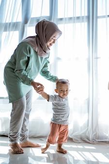 Мать помогает сыну идти на первый шаг