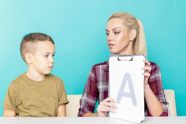 孤立したピンクの背景の上の宿題で彼女の息子を助ける母。遠隔教育。