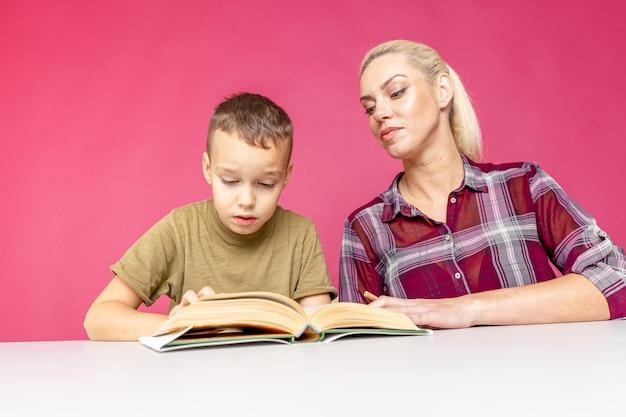 격리 된 분홍색 배경 위에 숙제와 그녀의 아들을 돕는 어머니. 먼 교육.