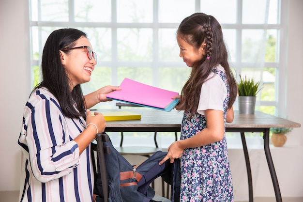 Mother helping primary school girl packing books to the bags