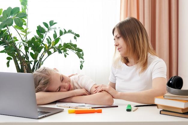 悲しい娘が宿題をするのを助ける母