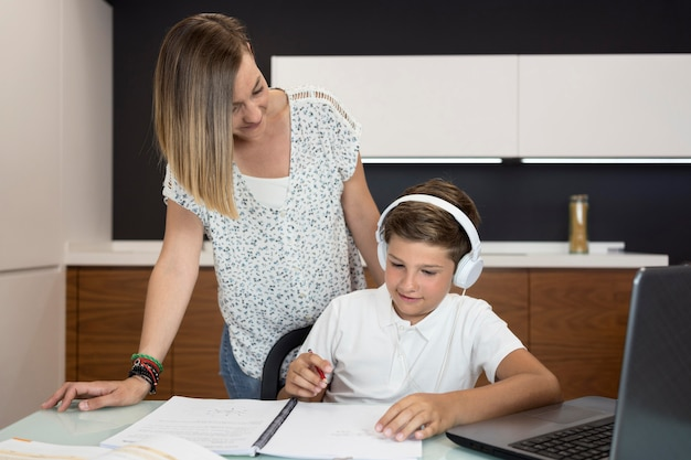 Mother helping son to finish homework