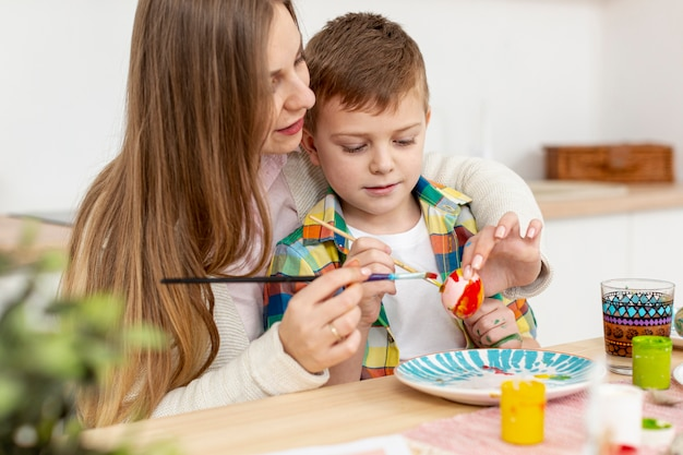 Mother helping son to paint eggs