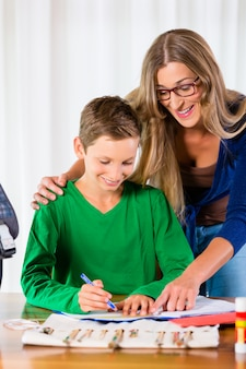 Mother helping son with homework assignment