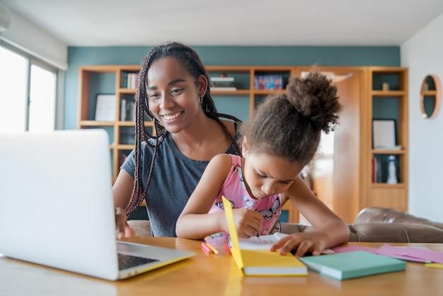 Madre che aiuta e sostiene sua figlia con la scuola online mentre è a casa. nuovo concetto di stile di vita normale. concetto monoparentale.